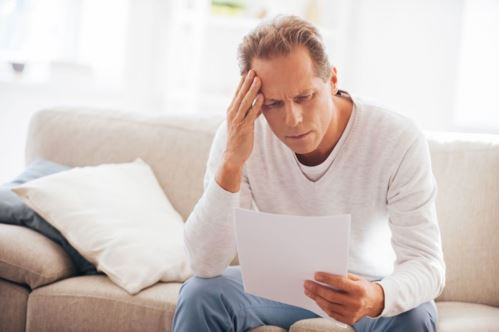 man looking frustrated at utility bill